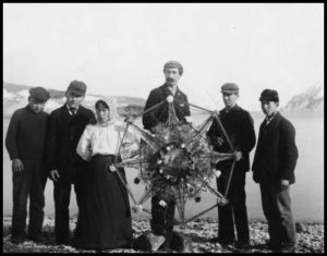 A group of people hold a Russian Christmas star on a beach in Unalaska in the early 1900s.