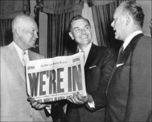 """Alaska Territorial Gov. Michael Anthony """"Mike"""" Stepovich, center, holds a newspaper proclaiming Alaska's admission to the Union as President Dwight D. Eisenhower, left, and then-U.S. Rep. Gerald Ford look on in 1958."""