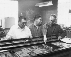 Howard Rock, left, along with Theodore Hetzel and Tom Snapp discuss printers' type blocks and plates.